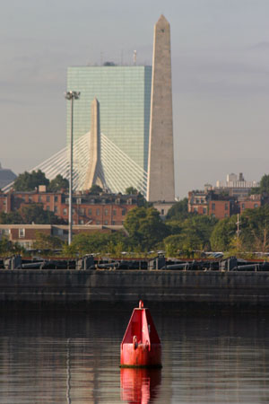 The Boston skyline provides the backdrop for a navigational aid (channel marker) in the Mystic River.