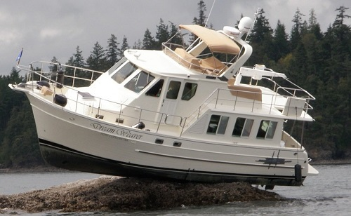 Cabin cruiser sits on the rocks at low tide