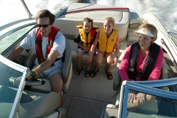 Family on a power boat wearing PFDs