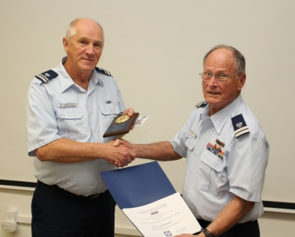 Roy Zimmerman (L) receives two awards at the April 12, 2016, Flotilla 12-09 meeting. They are from USCG Auxiliary 5th Northern District (5NR) for Service in Vessel Safety Checks, and from the Commendant of the Coast Guard for 60 Vessel Examintions during 2015. Both awards presentation by Flotilla 12-09 Commander Richard Stevenson (R).