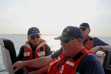 Coast Guard Station Indian River BMC J. Pond (center) oversees training exercises on two CG 47' Motor Lifeboats (MLB) while Auxiliarists Richard Stevenson (Flotilla 12-09 Commander), left, and Auxiliarist Mike McGuire (rear) observe.