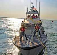 Coast Guard members receive a heaving line from the other MLB in preparation for transferring a line for a towing.