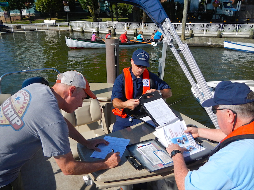 A boat owner signs a Vessel Safety Check form with members of flotilla 2 5 O 8