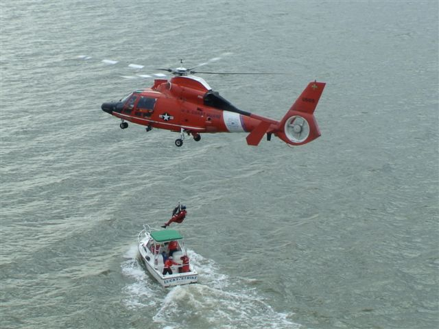 Photo of USCG helo hoisting a swimmer to/from crew aboard the USCG aux vessel lucky strike. Taken from a second helo at higher altitude.