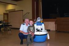 A man is a Coast Guard Auxilairy Uniform standing next to a child and a blue and white Coast Guard Boat Robot
