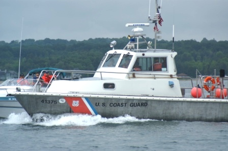 A Silver and White U.S. Coast Guard Boat on the water next to a smallwe white boat filled with People in Coast Guard Auxiliary Uniforms and Orange Life jackets