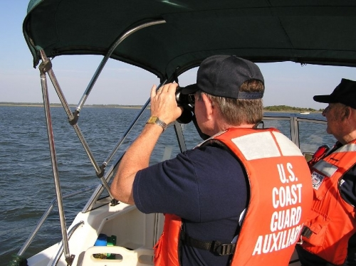 Three men in Coast Guard Auxiliary Uniforms and life Jackets on the Deck of a private Boat surveying the water