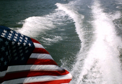 View from the back of a fast moving boat an American Flag over the wake of the boat