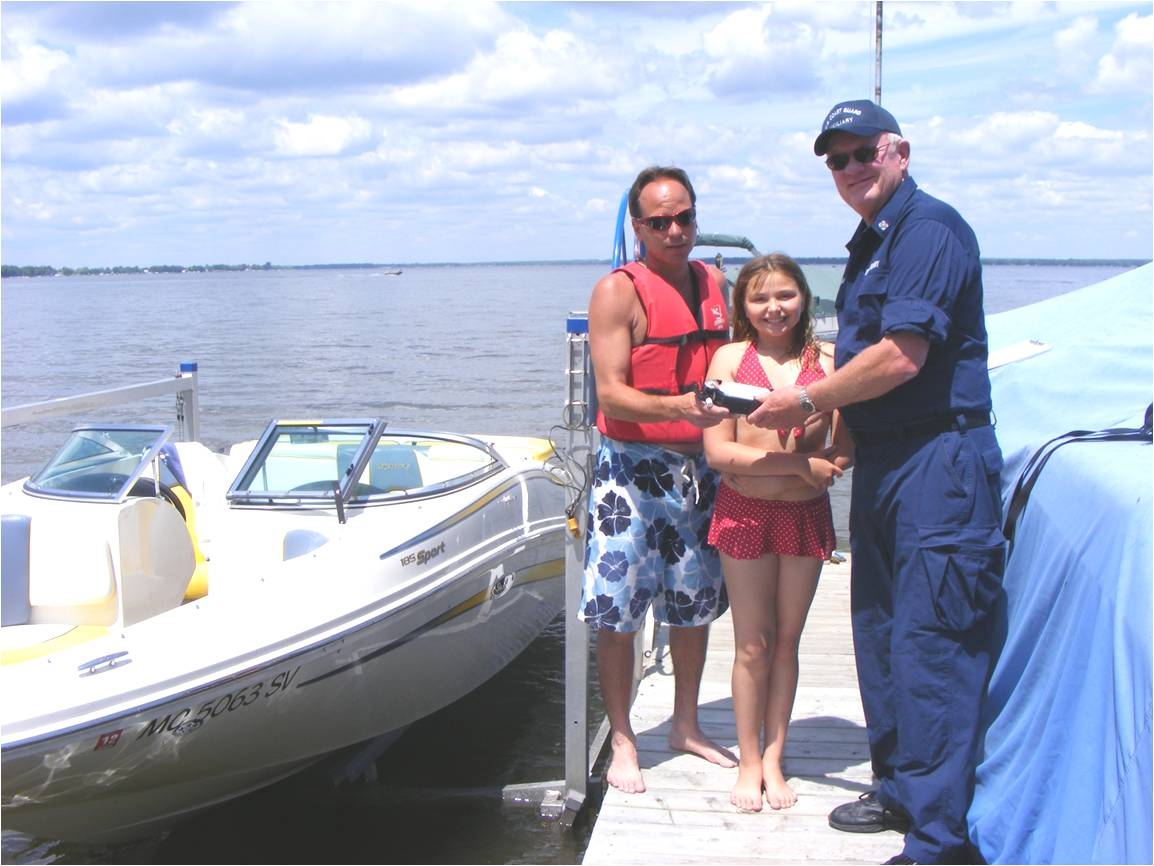 Man IN Coast Guard Auxiliary Uniform  talking to a man and a young girl both in bathing suits on a dock  with a boat next  to the dock