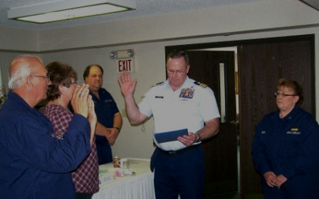 A man and a woman being sworn in by a man in a Coast Guard Uniform with other members of the Auxiliary looking on