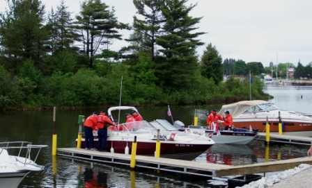 Three Coast Guard AuxiliaryBoats lined up at Docks with Many people in Auxiliary life Jackets ready to get out on the Water