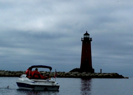 small white and blue Coast Guard Boat in front of a red lighthouse with a black roof.  In front of the boat is a small loon watching the people on the boat