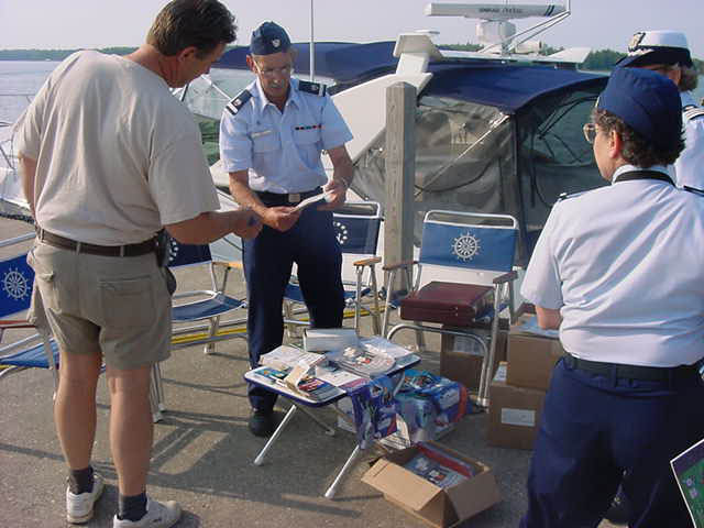 A man in an Auxiliary Uniform and a woman in an Auxiliary Unform discussing information with a member of the boating public