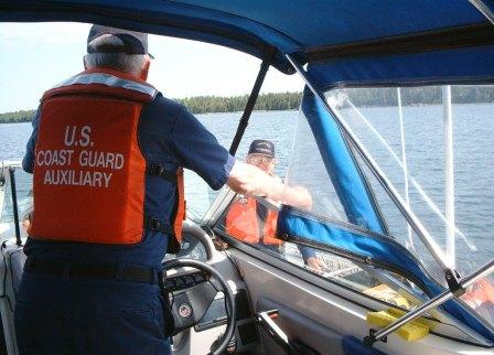 Two Men in Auxiliary Uniforms and life jackets in discussion on Two Separate Boats
