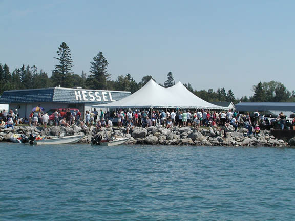 Scene of a large number of people under a white tent at the Hessel Boat Show