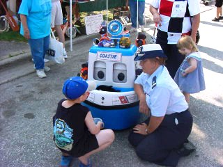 A woman is a Coast Guard Auxiliary Uniform with a young boy in front of a small Coast Guard Boat which is a robot