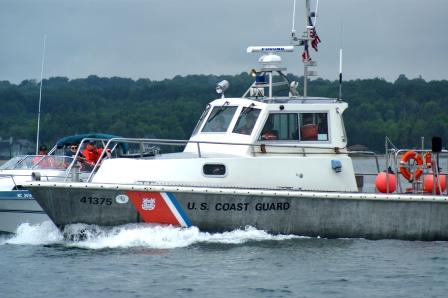 Large Grey and white  Coast Guard Boat Next to a smailler white Boat with Coast Guard Auxilairy members on board
