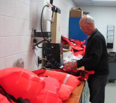 Man in front of a table inspecting orange life jackets