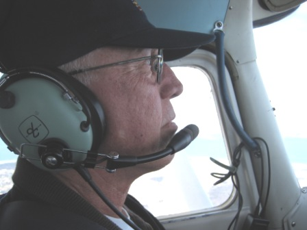 head shot of a man from the cockpit of any airplane he is wearing an Auxiliary Baseball cap and a set of head phones