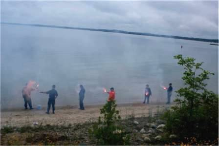 Several persons in Auxiliary Uniforms standing on the shore of a large lake holding flares. It is a very foggy day