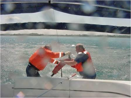 Two men in Auxiiliary life jackets on the stern of a boat struggling with a line obviously in a windy environment