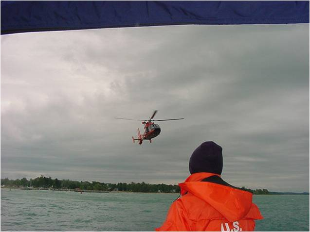 Man in an orange Coast guard life jacket and black knit cap looking at a helicopter in the near distance