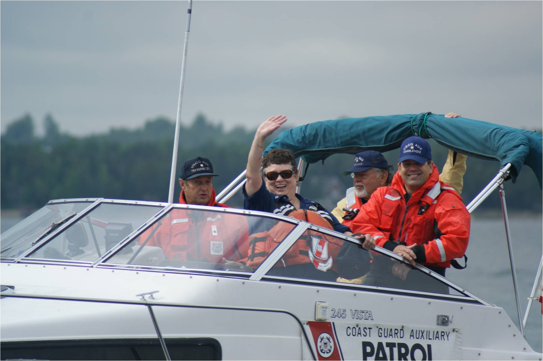 A Group of people on a Coat Guard Auxiliary Patrol Boat  in orange life jackets waving while enjoying the ride.