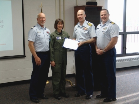 Woman in a olive green flight suit surrounded by three men in navy blue slacks and light blue uniform shirts