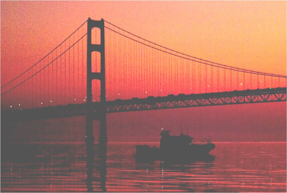 Picture of an Auxiliary Boat Crossing under the Mackinaw Bridge at Dawn with the sun rising in the background