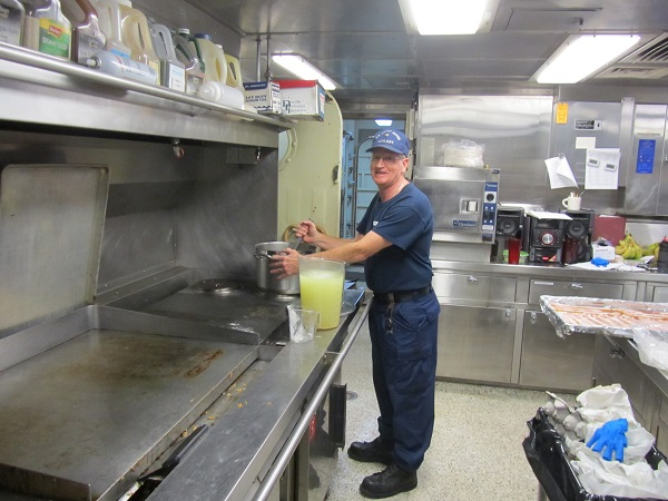 Auxiliarist cooking on USCG Cutter