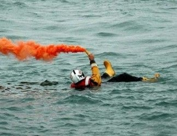 Picture of a person in the water holding a flare with orange smoke