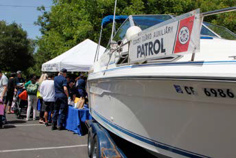 Picture of people at a booth near an Auxiliary patrol boat