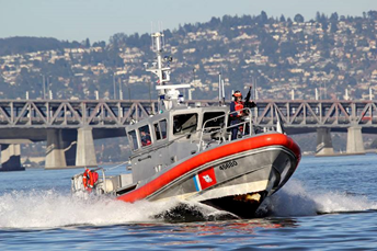 Picture of a Coast Guard patrol boat with a uniformed Coast Guardsman manning a gun