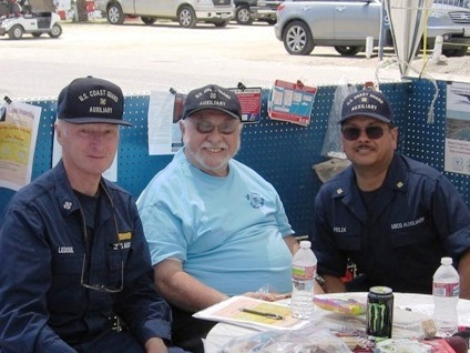 3 auxiliarists sitting in display booth