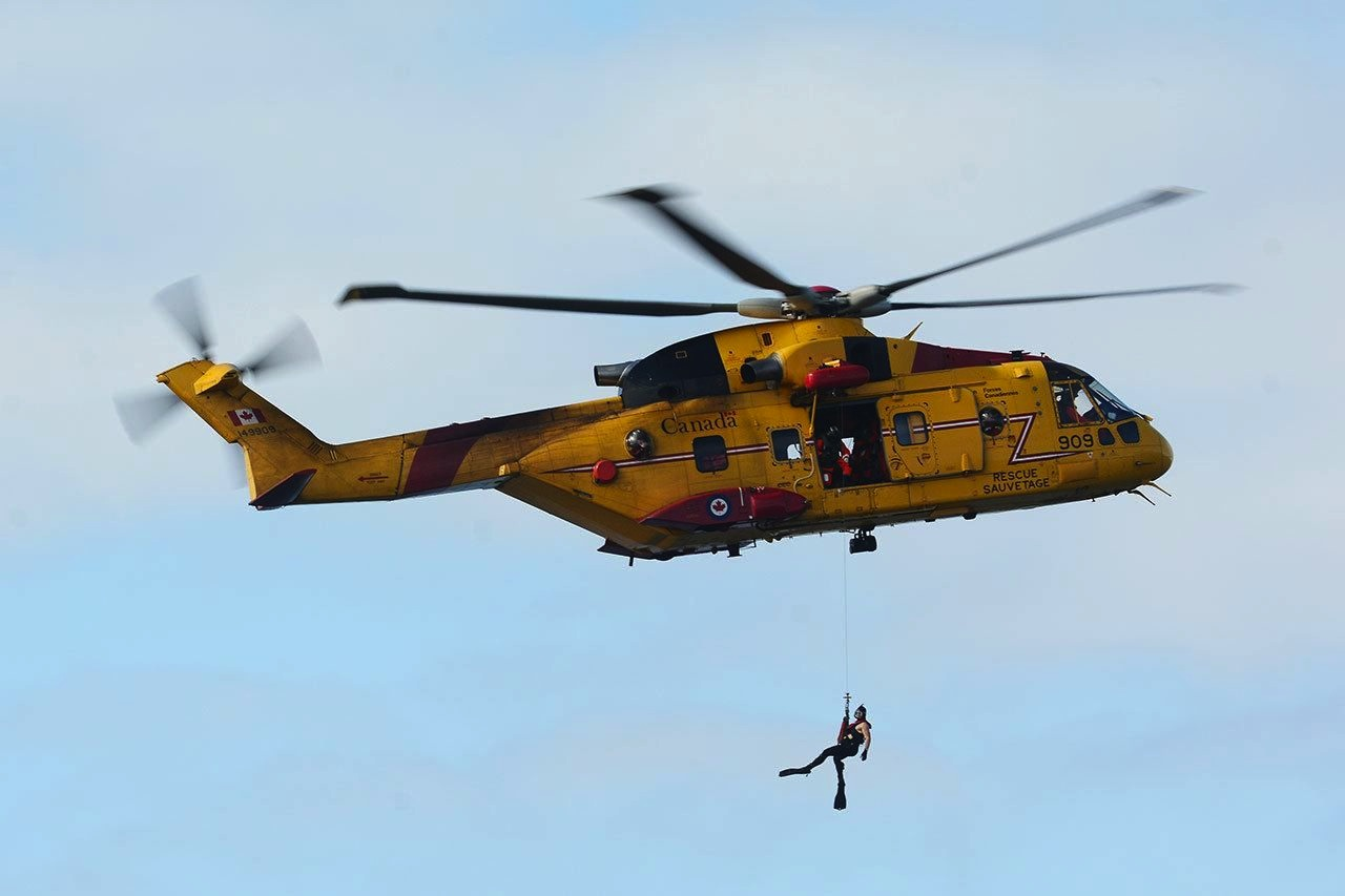 person dangling from helicopter